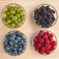 Variation of berries gooseberry blackberries blueberries raspberries in a glass bowls on wooden table close up Stock Photography