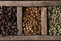 Variation of coffee beans food background with green and brown decaf unroasted and black roasted in old wooden box top view close Stock Photography
