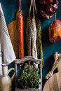 Variety of charcuterie sausages hanging on twine on hooks, wood cutting bard, herbs, linen towel, kitchenware Royalty Free Stock Photo