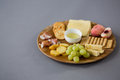 Variety of cheese with grapes, peach, meat and crackers Royalty Free Stock Photo