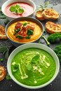 Variety of cream soup bowls: sweet pea and mint, tomato and basil and butternut squash with steamed kale and fried Royalty Free Stock Photo