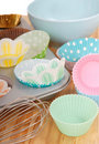 Variety of cupcake liners with wire whisk Royalty Free Stock Images