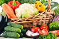 Variety of fresh organic vegetables in wicker basket composition with Stock Photos