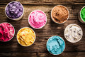 Variety of gourmet flavours of italian ice cream selection in vibrant colors served in individual plastic tubs on an old rustic Royalty Free Stock Images