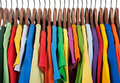 Variety of multicolored clothes on wooden hangers Royalty Free Stock Photography