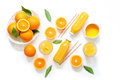 Variety of orange juice in bottles and glasses, straws, oranges isolated on white background top view. Royalty Free Stock Photo
