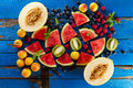 Variety of tasty fresh healthy appetizing fruits on blue wooden