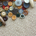Variety of vintage buttons on fabric background a different size and shape sewing are scattered in the corner bordering a woven Royalty Free Stock Photos