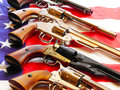 Various antique handguns american flag as background Royalty Free Stock Photography