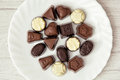 Various belgian pralines on the white plate, sweet food Royalty Free Stock Photo