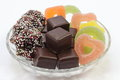 Various christmas goodies on glass plate like dominos jelly fruits and fudge stars a white background Stock Photos