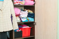 Various color clothes are organized at shelves in wardrobe open Stock Images