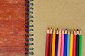 Various color pencils and note book Stock Photos