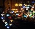 Various colorful round shaped retro glass lamps in darkness, in the market, as vintage color effect