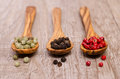 Various coloured pepper on a wooden spoon Stock Image