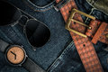 Various fashions of sunglasses wrist watches and belt in jeans Royalty Free Stock Photos