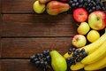 Various fruits apples pears bananas grapes on a wooden background Stock Image