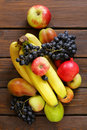 Various fruits apples pears bananas grapes on a wooden background Royalty Free Stock Images