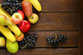 Various fruits apples pears bananas grapes on a wooden background Stock Images
