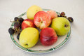 Various fruits on plate fresh and colored apples grapes and nectarines on table white Stock Photo
