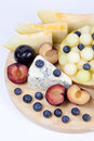 Various fruits on the plate melon blueberries lying plums and cheese Royalty Free Stock Photography