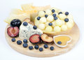 Various fruits on the plate melon blueberries lying plums and cheese Royalty Free Stock Image