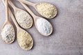 Various gluten free flour wooden spoons of almond amaranth seeds buckwheat rice chick peas from top Stock Photo