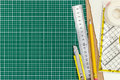 Various office supplies on green cutting mat. working desk view Royalty Free Stock Photo