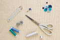 Various sewing items including scissors tailors wheel bobbins spools of thread measuring tape thimble and buttons in harmonising Stock Image