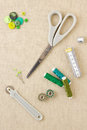 Various sewing items including scissors tailors wheel bobbins spools of thread measuring tape thimble and buttons in harmonising Royalty Free Stock Image