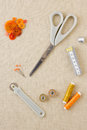 Various sewing items including scissors tailors wheel bobbins spools of thread measuring tape thimble and buttons in harmonising Royalty Free Stock Images