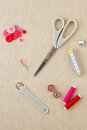 Various sewing items including scissors tailors wheel bobbins spools of thread measuring tape thimble and buttons in harmonising Royalty Free Stock Photo