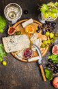 Various soft cheeses light and dark grapes on a cutting board with a knife for cheese peach wine glasses on wooden rustic backgrou Royalty Free Stock Photo