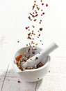 Various spices falling into mortar and pestle Royalty Free Stock Photo