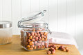 Various sugared nuts in jar on kitchen table Royalty Free Stock Image