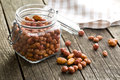 Various sugared nuts in jar on old wooden table Royalty Free Stock Photography