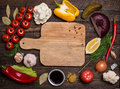 Various vegetables and spices and empty old cutting board. Color Royalty Free Stock Photo
