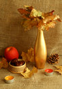 Vase with dry leafs, apple and candles on sacking Stock Image