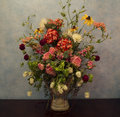 Vase of flowers against blue wall Royalty Free Stock Photo