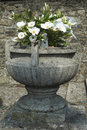 Vase with flowers door in cement white in front of the church of san biagio inverigo italy Stock Photo