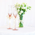 Vase of flowers and wedding glasses on the table Stock Images