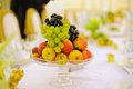 Vase with fruits glass on table Stock Photography
