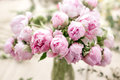 Vase of peonies in the foreground. soft focus. Workshop florist, making bouquets and flower arrangements. Woman Royalty Free Stock Photo