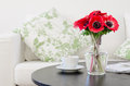 Vase of red flowers in modern white living room Royalty Free Stock Image