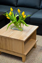 Vase yellow spring tulips modern wooden coffee table Royalty Free Stock Photo