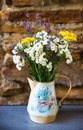 Vase with yellow, white and violet blooming meadow flower. Royalty Free Stock Photo