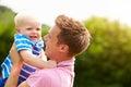 Vater hugging young son im garten Stockbilder