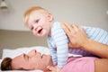 Vater playing with baby sohn wie sie im bett zusammen liegen Stockfotografie