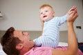 Vater playing with baby sohn wie sie im bett zusammen liegen Stockfoto