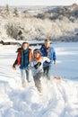 Vater und Kinder, die Schlitten herauf Snowy-Hügel ziehen Lizenzfreies Stockfoto